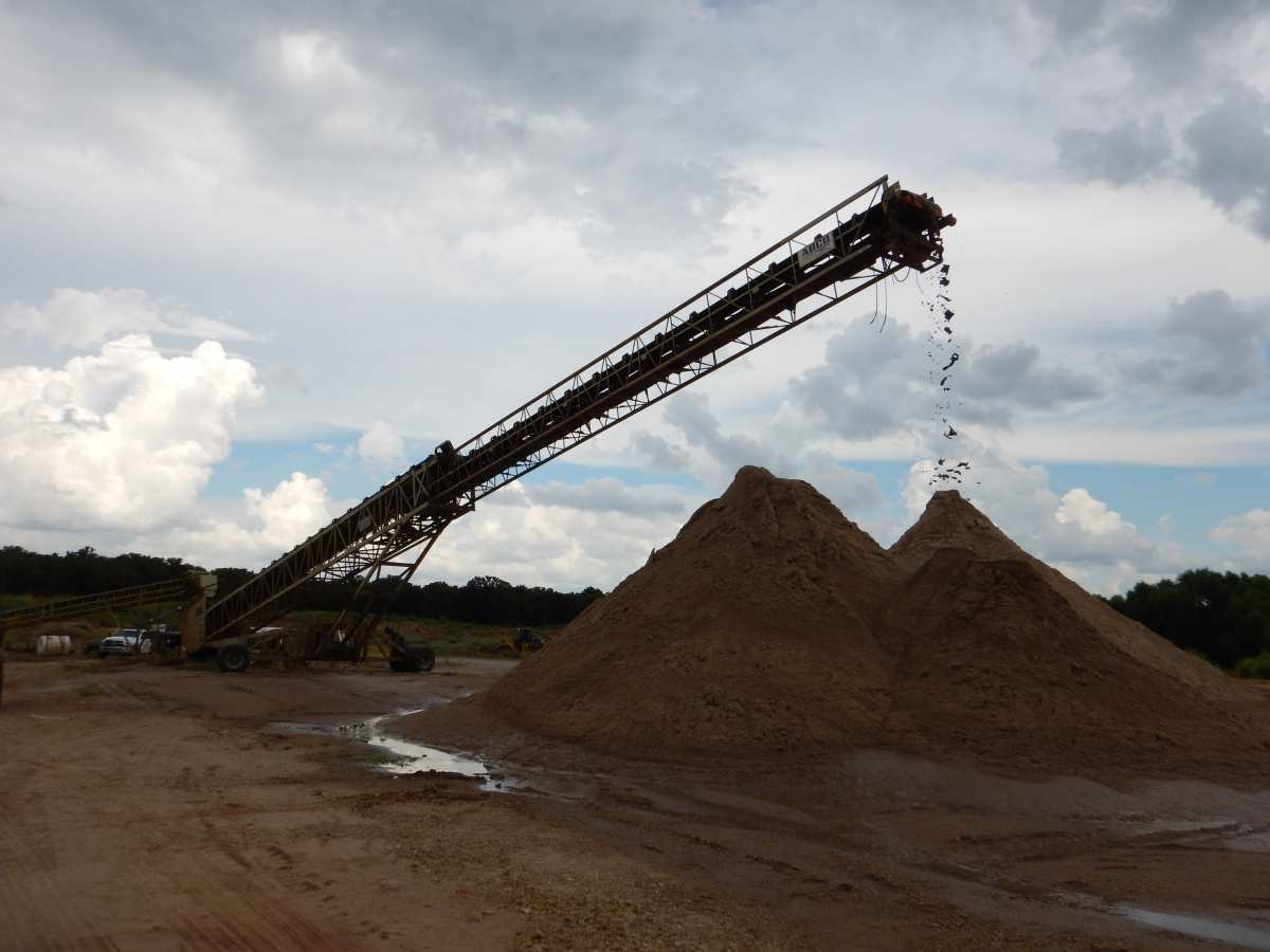 A telescoping conveyor delivers washed and sized sand particles to the stockpiles.